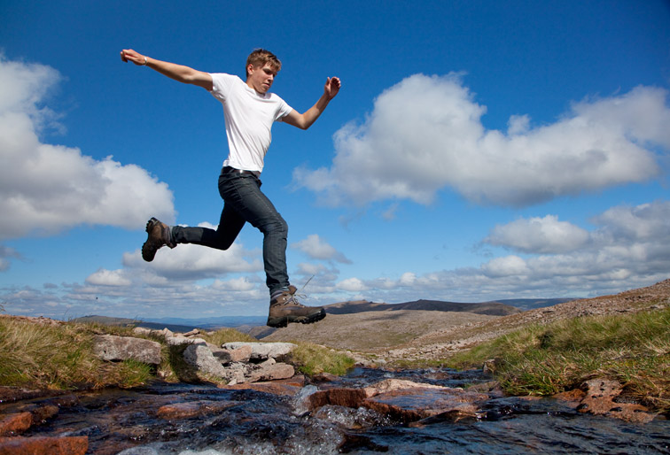 Boy (aged 17) jumping across upland stream, Cairngorms National Park, Scotland, August